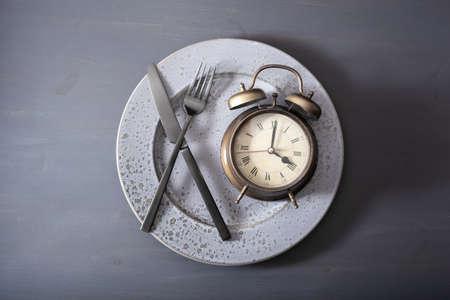 concept van intermitterend vasten, ketogeen dieet, gewichtsverlies. wekker vork en mes op een bord Stockfoto