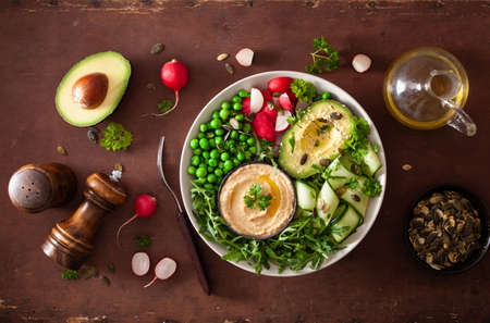 healthy vegan lunch bowl with avocaco cucumber hummus peas radish