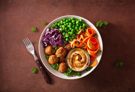 healthy vegan lunch bowl with falafel hummus carrot ribbons cabbage and peas Stockfoto
