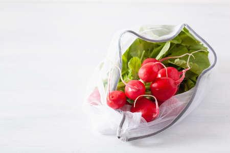 radish vegetable in reusable mesh nylon bag, plastic free zero waste concept
