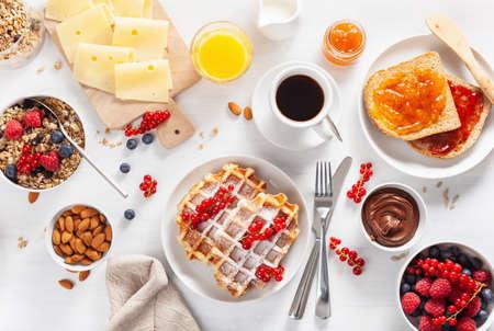 Frühstück mit Müsli-Beeren-Nüssen, Waffel, Toast, Marmelade, Schokoladenaufstrich und Kaffee. Draufsicht Standard-Bild