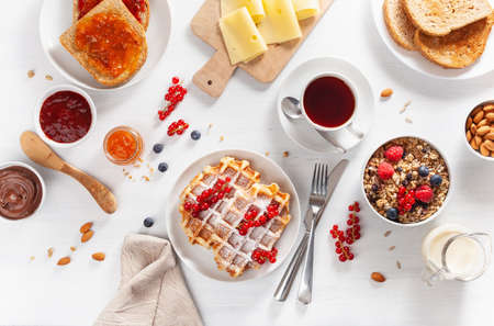 breakfast with granola berry nuts, waffle, toast, jam, chocolate spread and coffee. Top view