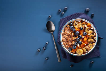 chocolate oatmeal porridge with blueberry, nuts, banana, dried apricot for healthy breakfast. Top view