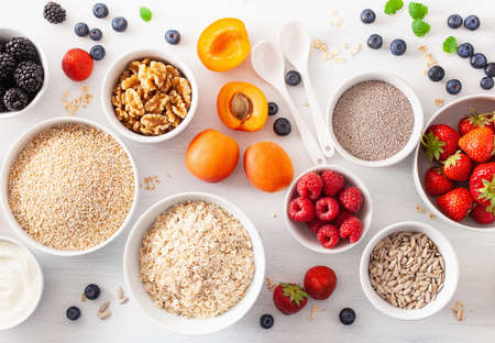 variaty of raw cereals, fruits and nuts for breakfast. Oatmeal flakes and steel cut, barley, walnut, chia, apricot, strawberry. Healthy ingredients