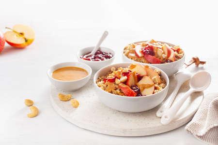 Bol de quinoa au beurre de cacahuète et aux pommes avec confiture et noix de cajou pour un petit-déjeuner sain