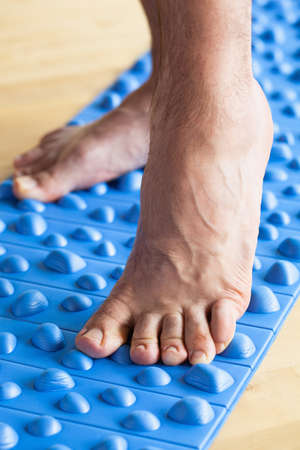 man doing flatfoot correction gymnastic exercise walking on massage mat at home