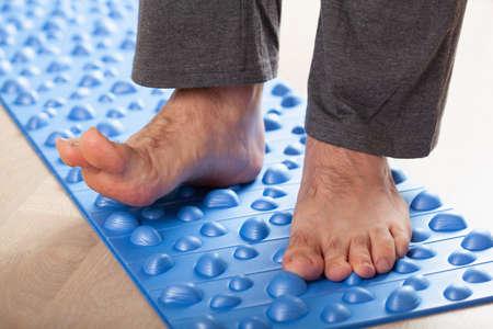 man doing flatfoot correction gymnastic exercise walking on massage mat at home