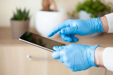 man hands in gloves using tablet computer, preventing germs coronavirus bacteria