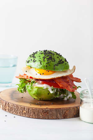 keto paleo diet avocado breakfast burger with bacon, egg, tomato Standard-Bild