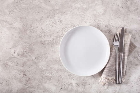 empty plate fork knife on concrete background