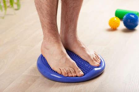 man doing flatfoot correction gymnastic exercise balancing on massage cushion at home