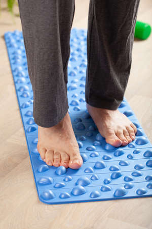 man doing flatfoot correction gymnastic exercise walking on massage mat at home Stockfoto