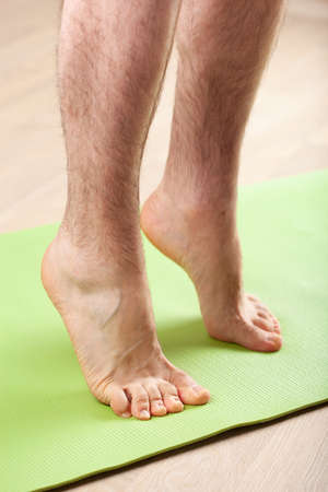 man doing flatfoot correction gymnastic exercise standing on toes at home Stockfoto