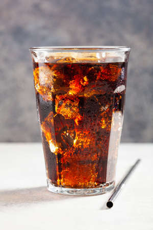 glass of cold cola soft drink with ice on wooden background