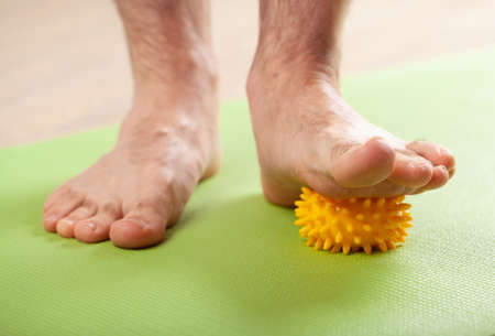 man doing flatfoot correction gymnastic exercise using massage ball at home
