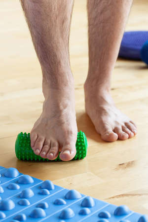 man doing flatfoot correction gymnastic exercise using massage roller at home Stockfoto