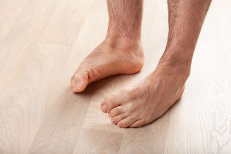 man doing flatfoot correction gymnastic exercise at home