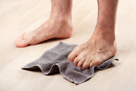 man doing flatfoot correction gymnastic exercise grabbing towel at home Stock Photo