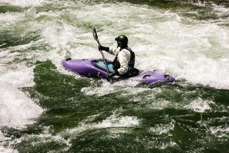 Whitewater kayaker negotiating river rapids in Northern California