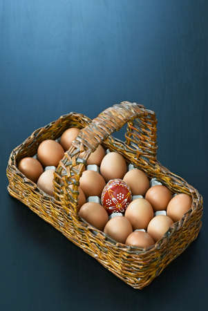 wooden basket with eggs and one Easter red egg