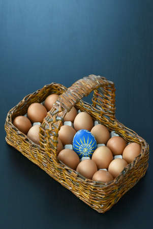 wooden basket with eggs and one Easter blue egg