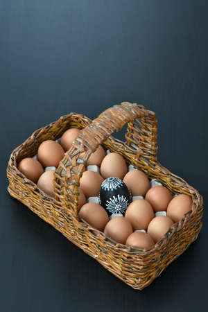 wooden basket with eggs and one Easter black egg