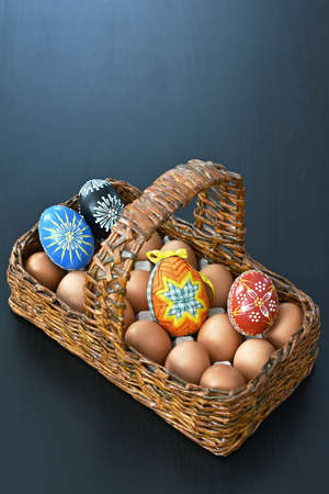 wooden basket with eggs and one Easter color egg