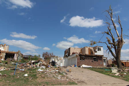 White clouds in beautiful blue skys bely the horrific tornado damage below. Stock Photo - 12410390