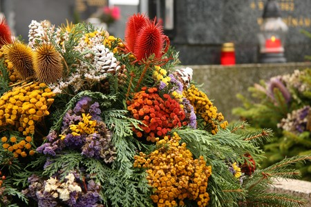 cemetry: funeral flower with candle and tomb stone in the background