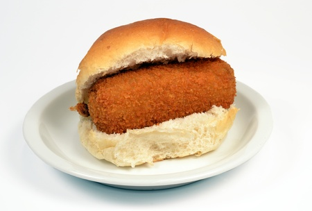 Roll with crispy calf croquette on a white context roll