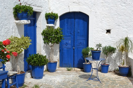 Typical greek courtyard with blue flower pots in Piskopiano on Crete, Greece. Editorial
