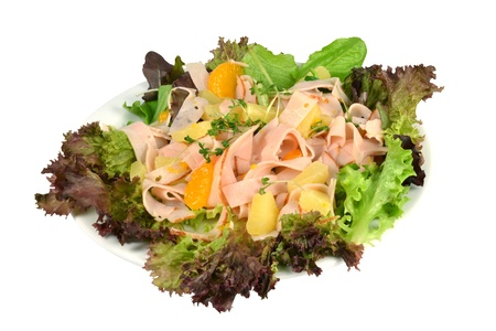 Cold salad with turkey strips and fruit on a white background.