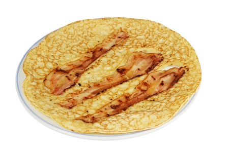 A board with a pancake with bacon strips on a white background  photo