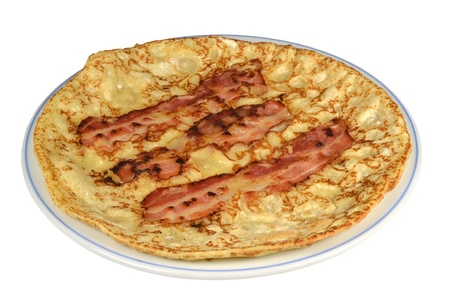 A board with a pancake with bacon rashers on a white background  Stock Photo