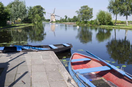 Typical Dutch vista with boats for rent and a mill in Klein Giethoorn in Hazerswoude, Netherlands