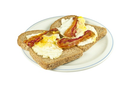 Two slices of brown bread with fried egg and bacon on a white background