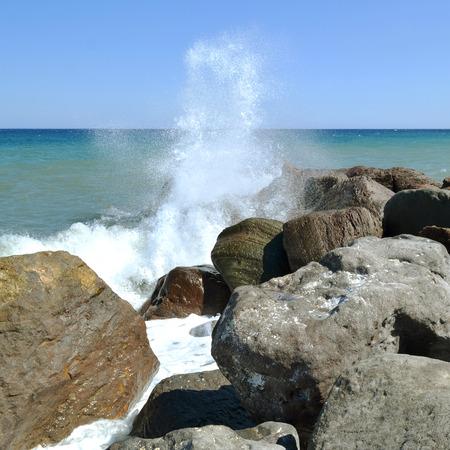Splashing sea water on the rocks on the beach in Kamari in Greece.