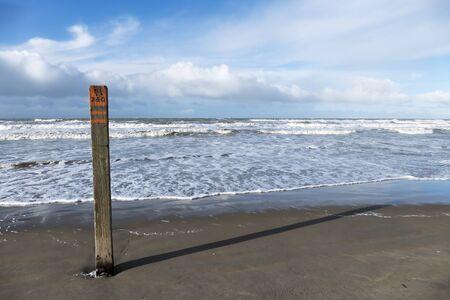 Beach Pole with long shadow on the empty beach of Wassenaar, Netherlands.