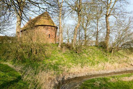 Mound with a church in Jannum in Friesland Netherlands. Reklamní fotografie