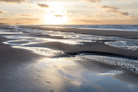 the flood tide: Sunset on the beach at Wassenaar in the Netherlands.