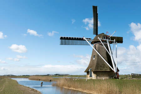 cultural history: NETHERLANDS  JANNUM  CIRCA APRIL 2015: Frisian polder with mill.