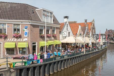 lemmer: NETHERLANDS - LEMMER - CIRCA AUGUST 2015: People on a terrace in the center of Lemmer.