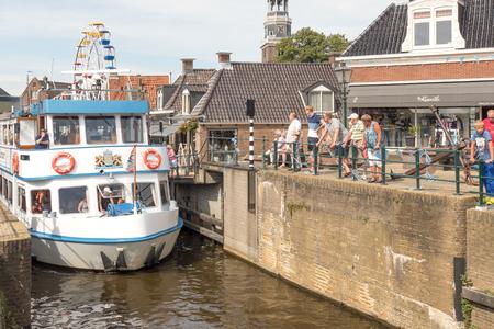 lemmer: NETHERLANDS - LEMMER - MEDIA AUGUST, 2015: Tour boat by the old lock in Lemmer in Friesland in the north of Netherlands.