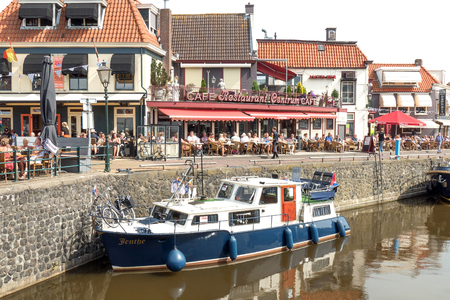 lemmer: NETHERLANDS - LEMMER - MEDIA AUGUST 2015: Sailing yacht in the port of Lemmer with people on the terrace in Friesland, Netherlands. Editorial