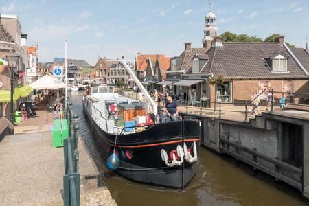 lemmer: NETHERLANDS - LEMMER - MEDIA AUGUST, 2015: Boat by the old lock in Lemmer in Friesland in the north of Netherlands.