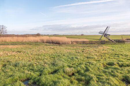 cultural history: Meadow with Paaltjasker windmill in nature area Sanpoel in Friesland, Netherlands.