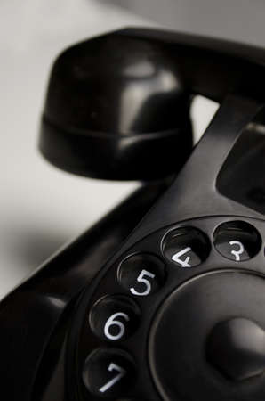 bakelite: Old black Bakelite telephone (Type 1955 by PTTHEEMAF) with rotary dial on white background Stock Photo