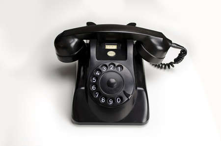bakelite: Old black Bakelite telephone (Type 1955 by PTTHEEMAF) with rotary dial, isolated on white background.