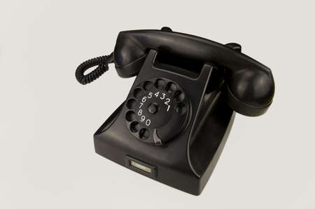 bakelite: Old black Bakelite telephone (Type 1951 by PTTSiemens) with rotary dial, isolated on white background.