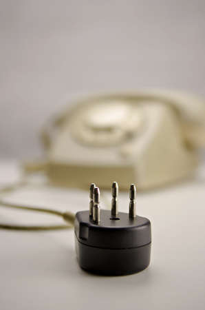 unplugged: Unplugged classic gray  kaki telephone (T65 by PTTSiemens) with rotary dial on white surface. Black connector unplugged.